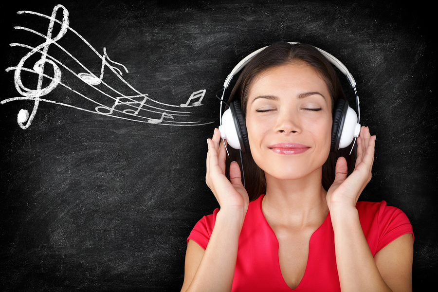 Music - woman wearing headphones listening to music with music notes drawn on black blackboard texture background. Serene relaxing beautiful young multiracial Asian Caucasian girl enjoying music.